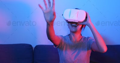 Woman play with VR device with purple and blue light