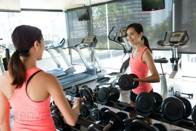 Fitness girl lifting dumbbell in the gym