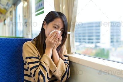 Woman sneezing on train