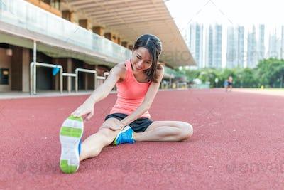 Sport woman stretching legs in sport stadium