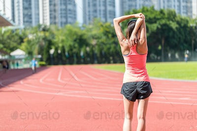 Woman stretching hand in red track stadium