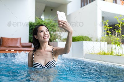 Woman enjoy in jacuzzi spa and taking selfie by mobile phone