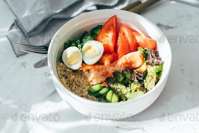 Fish salad bowl with salmon, couscous, salad mix, green beans, broccoli, tomatoes, quail eggs
