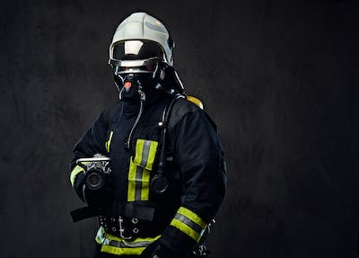 Firefighter dressed in uniform and an oxygen mask.