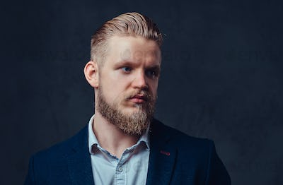Portrait of stylish blond bearded male dressed in a suit.