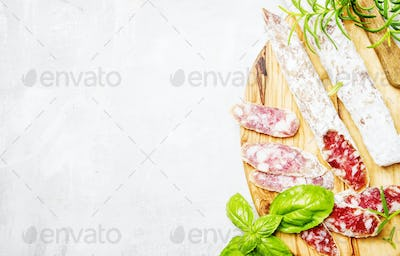 Pork sausages with rosemary and basil, gray background, top view