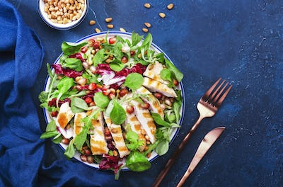 Salad with grilled chicken, spinach, arugula, cedar nuts and pomegranate seeds