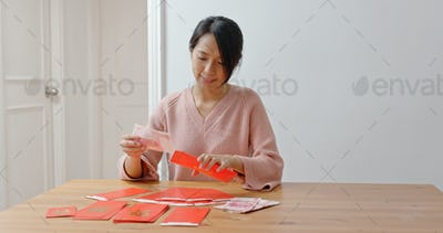 Woman fill money into red packet for lunar new year