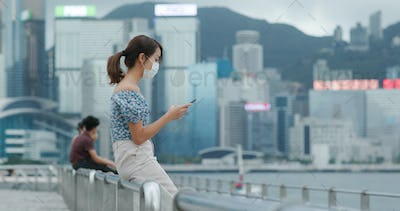 Woman wear face mask and use of mobile phone in Hong Kong