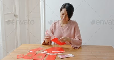 Woman putting money inside red packet