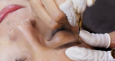 Cosmetologist applying permanent tattooing of eyebrows in beauty salon, Microblading procedure