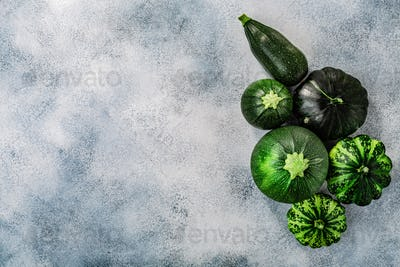 Green Summer squashes on washed concrete backdrop with copyspace,  top view