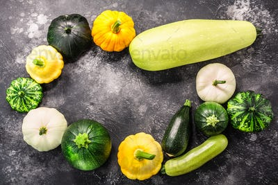 Summer squashes on textured concrete backdrop with copyspace,  top view