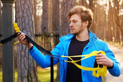 A man exercising with trx fitness strips.