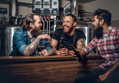 Stylish three men drinking craft beer in the microbrewery.