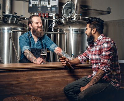 Caucasian and Indian men presenting craft beer in the microbrewery.