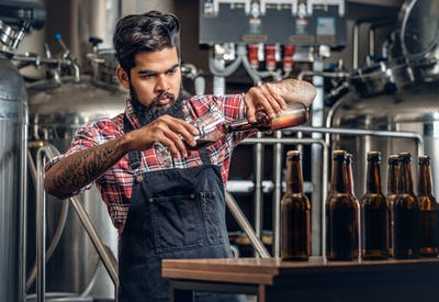 Indianr male manufacturer tasting and presenting craft beer in the microbrewery.