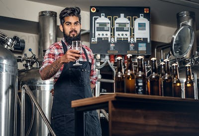 Indian male manufacturer presenting craft beer in the microbrewery.
