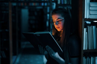 Imagination conception. Female student is in library that full of books. Conception of education