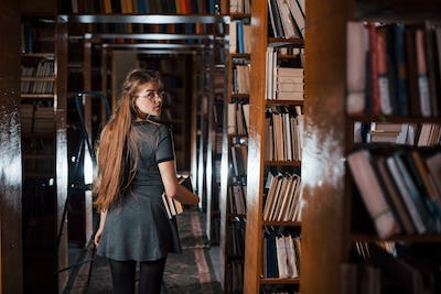 Looks behind. Female student is in library that full of books. Conception of education