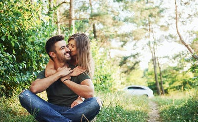 Sitting and embracing. Beautiful young couple have a good time in the forest at daytime
