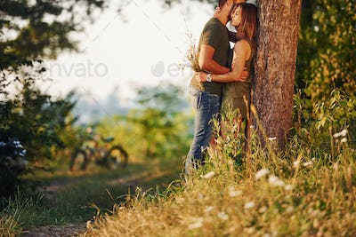Leaning on the tree. Beautiful young couple have a good time in the forest at daytime