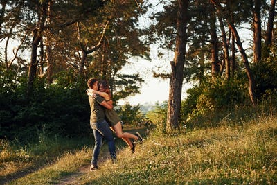 Beautiful young couple have a good time in the forest at daytime