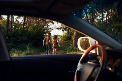 Steering wheel, side mirror. Beautiful young couple have a good time in the forest at daytime