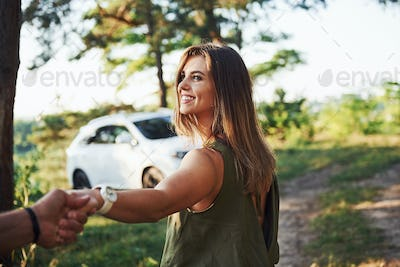 Holding by the hands. Beautiful young couple have a good time in the forest at daytime