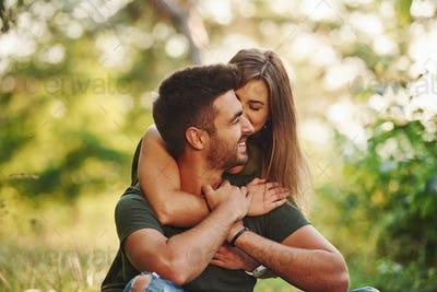 Closeness of people. Beautiful young couple have a good time in the forest at daytime