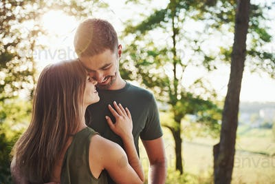 In casual clothes. Beautiful young couple have a good time in the forest at daytime