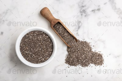 Chia seeds in wooden scoop and bowl on marble table