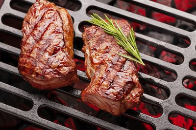 Beef steaks cooking on grill