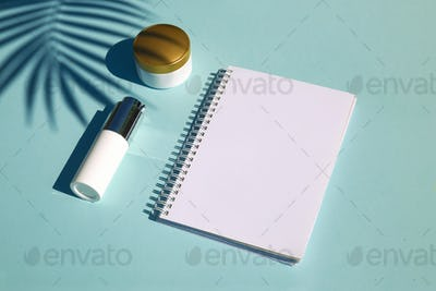 Cosmetic natural products on pastel blue background. Notebook for inscription
