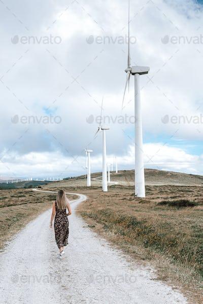 Woman walking by a wind turbine farm