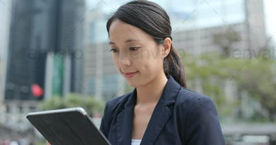 Businesswoman type on tablet computer in the city