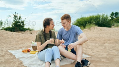 Young adult couple talking and having picnic on beach
