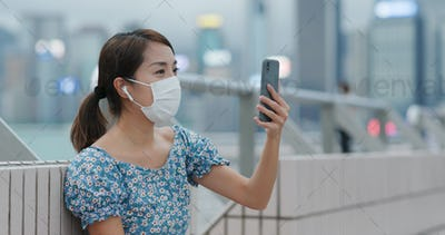 Woman chat on cellphone with video call and wear face mask at outdoor