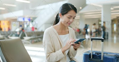 Woman checking flight number on mobile phone in the airport