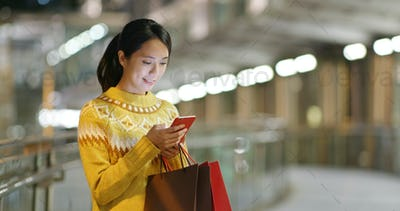 Woman holding with shopping bag and use of smart phone in city