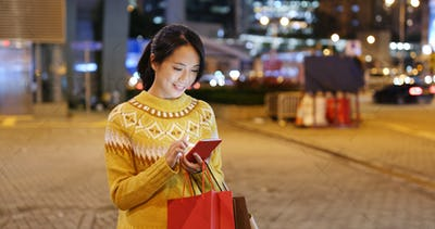 Woman use of mobile phone and holding with shopping bag at night