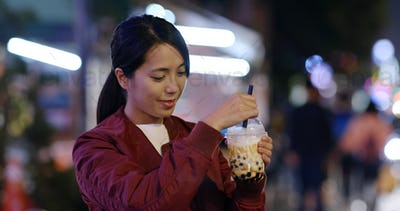 Woman enjoy iced bubble tea in city at night