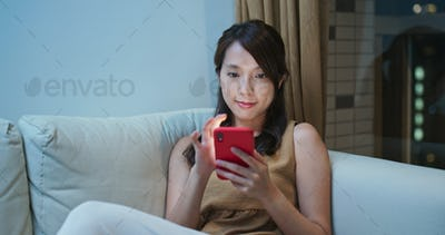 Woman sit on sofa and use of mobile phone for online