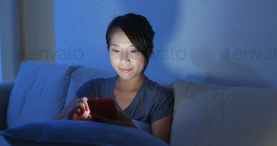 Woman use of mobile phone for surf online at home in the evening