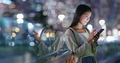 Asian woman use of mobile phone in city at night