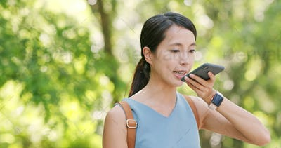 Woman sending audio message on cellphone in the park
