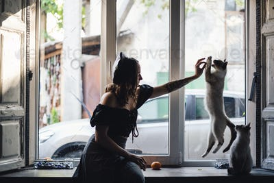 Pretty woman playing with siamese cats