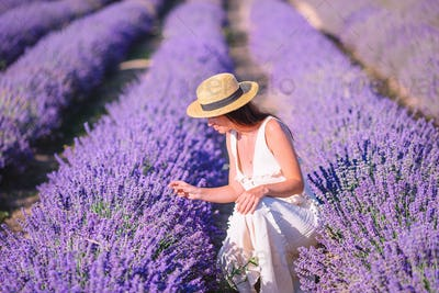Woman in lavender flowers field in white dress and hat