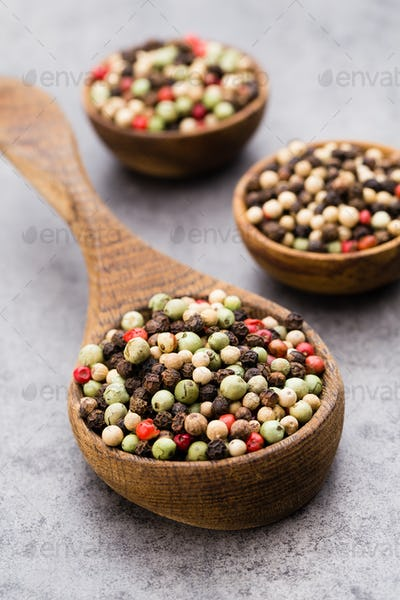 Peppercorn mix in a wooden bowl on grey table.
