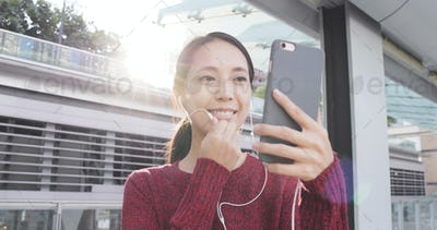Woman talking video call on cellphone with earphone at outdoor